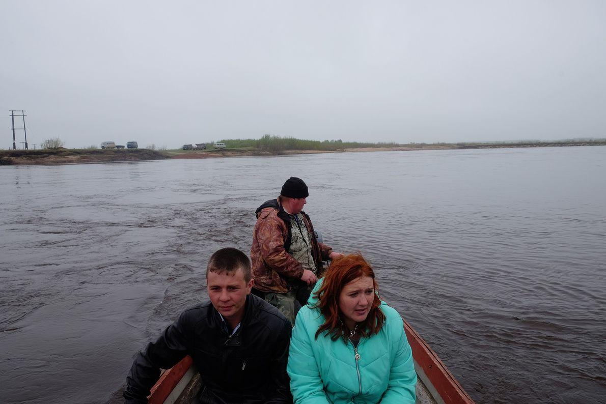 Una joven pareja de Byechye cruza el Río Mezén en un bote rocketa.