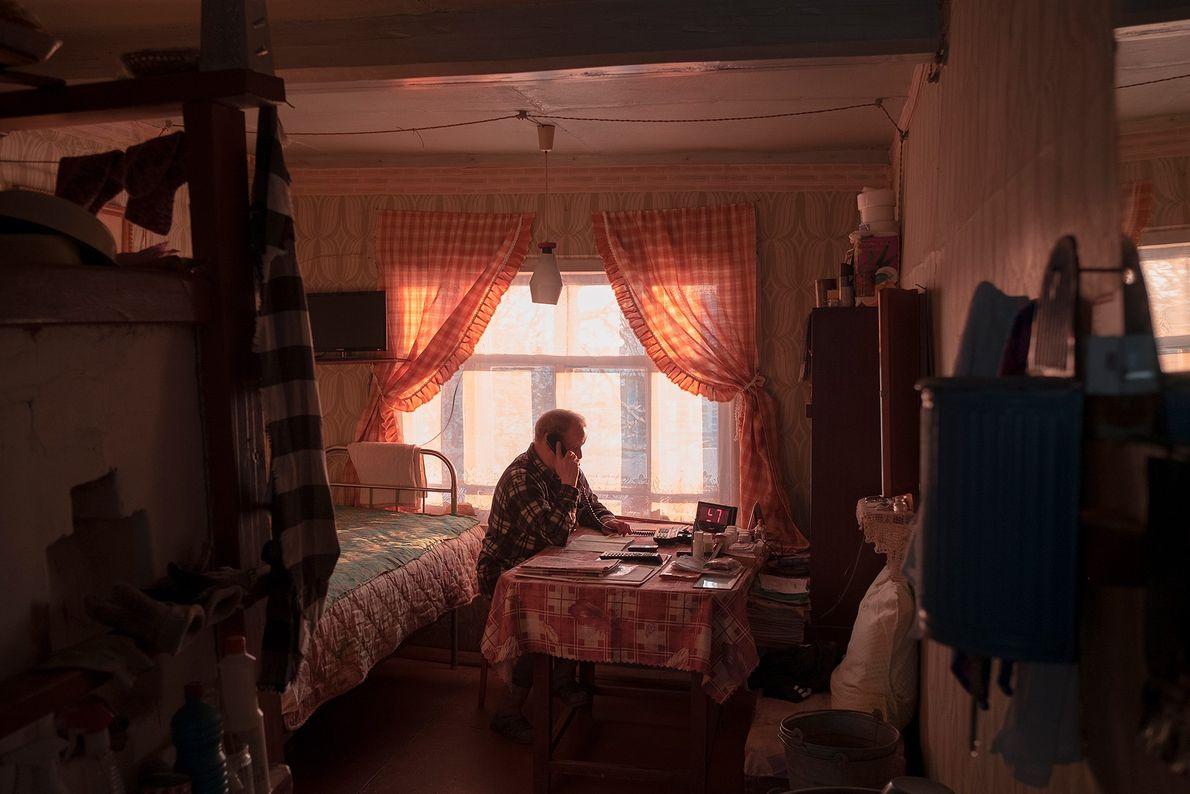 Vladimir, residente de Sovpolie, de 76 años, habla por teléfono en su casa.