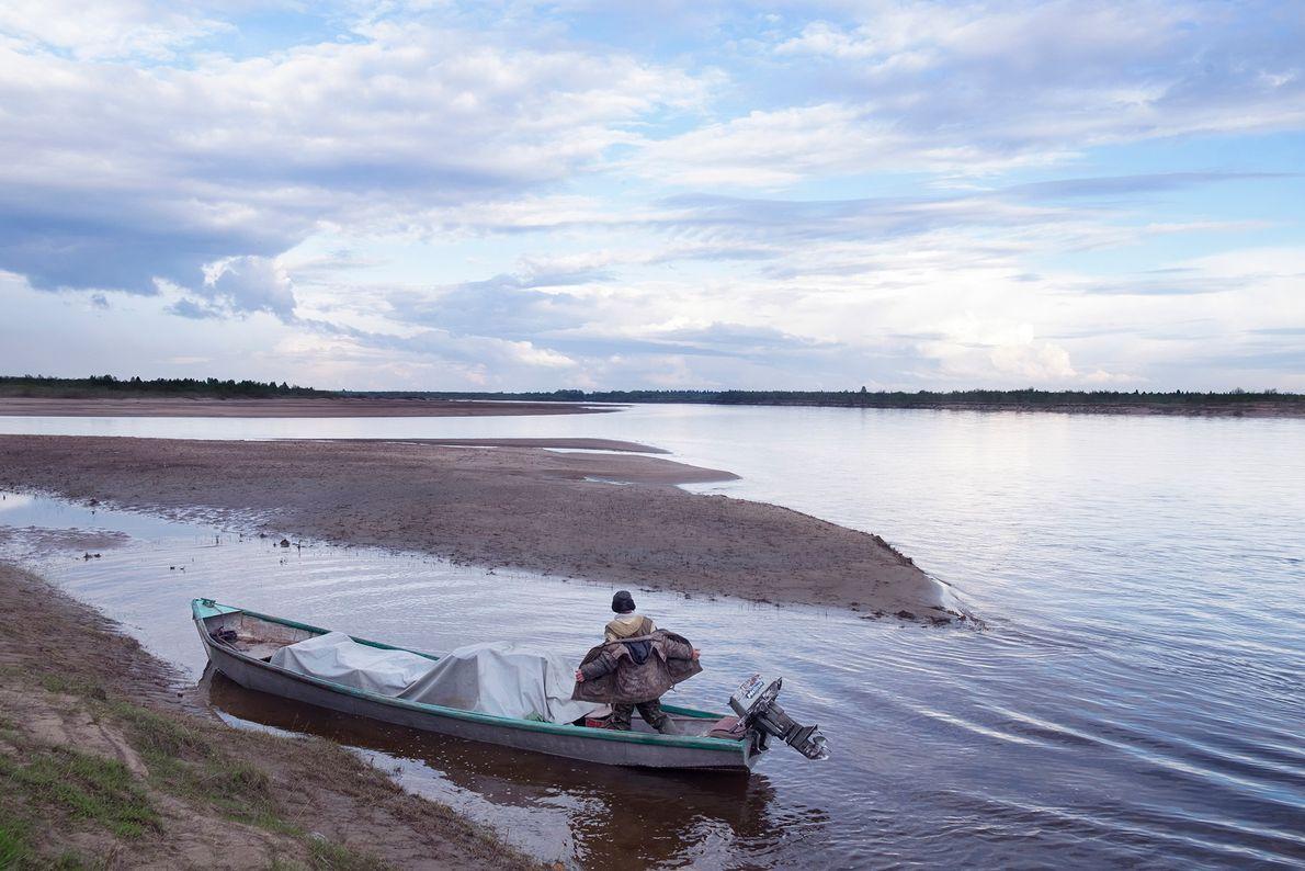 Un pescador en su bote rocketa toca tierra con su carga. Vive en un pueblo con ...