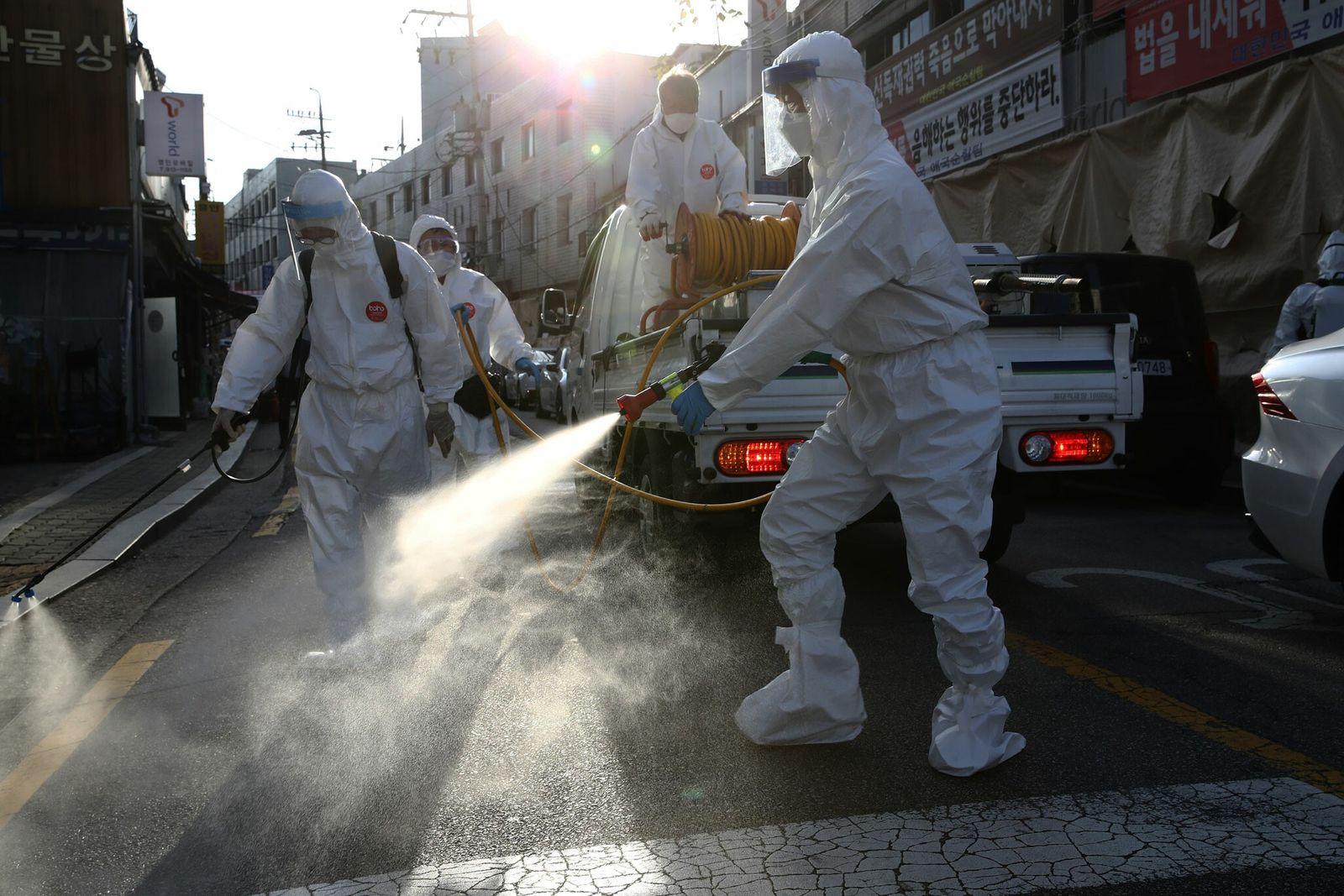Trabajadores de desinfección con equipo de protección personal limpian una calle para prevenir la propagación del ...