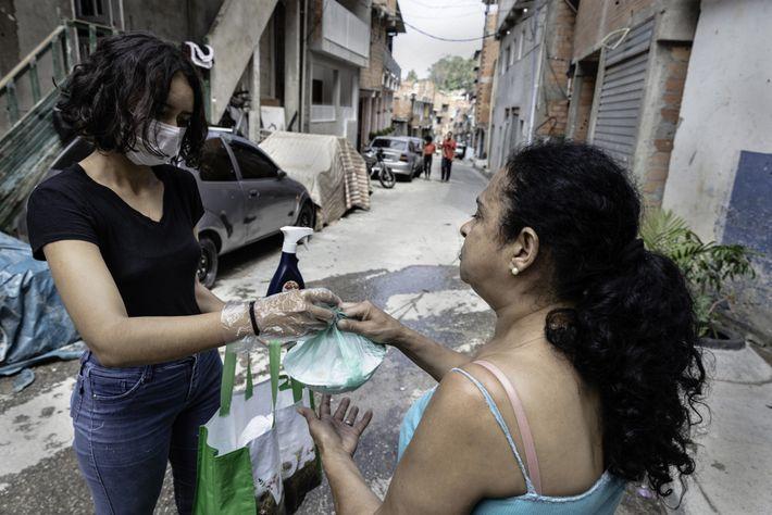 Maria Angelica de Araújo Costa entrega la comida y rocía desinfectante en las manos de una ...