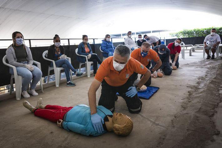 Los bomberos enseñan primeros auxilios a los miembros de la Unión de Residentes de Paraisópolis que ...