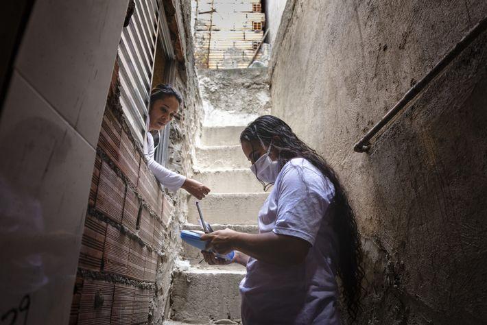 La voluntaria de la Unión de Residentes de Paraisópolis Amanda Barros Vasconcelos Silva, derecha, registra en ...