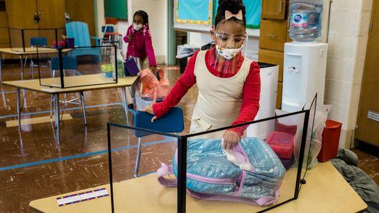 Los estudiantes toman sus asientos el primer día de jardín de infantes en persona en la ...
