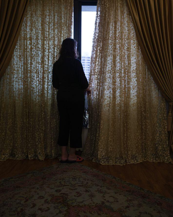 La madre de la autora, Jila, se para frente a la ventana de su habitación para ...