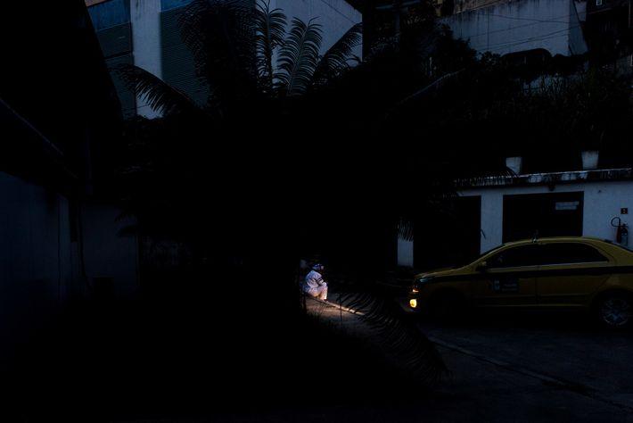 Una trabajadora de la salud toma un descanso, iluminada por las luces de un taxi que ...