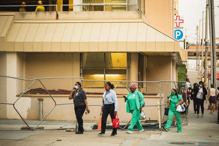 Trabajadoras de la salud llegan para su cumplir su turno en el Hospital Grady Memorial en ...