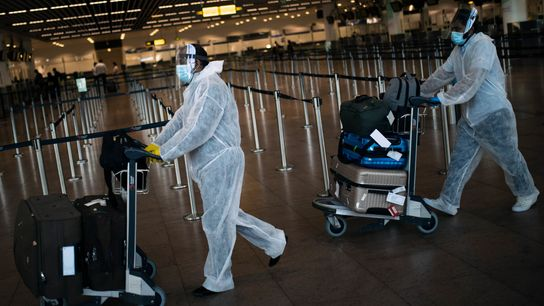 Pasajeros con trajes protectores transportan su equipaje por el Aeropuerto Internacional Zaventem en Bruselas, Bélgica, el ...