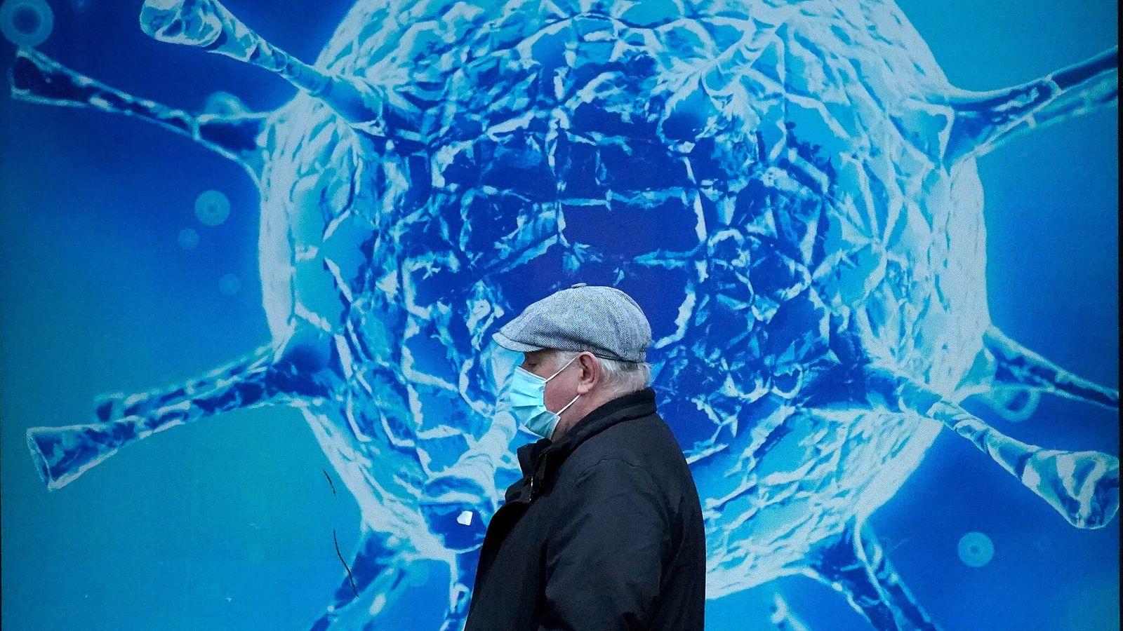 Un hombre con mascarilla protectora pasa caminando por una ilustración de un virus afuera del Centro ...