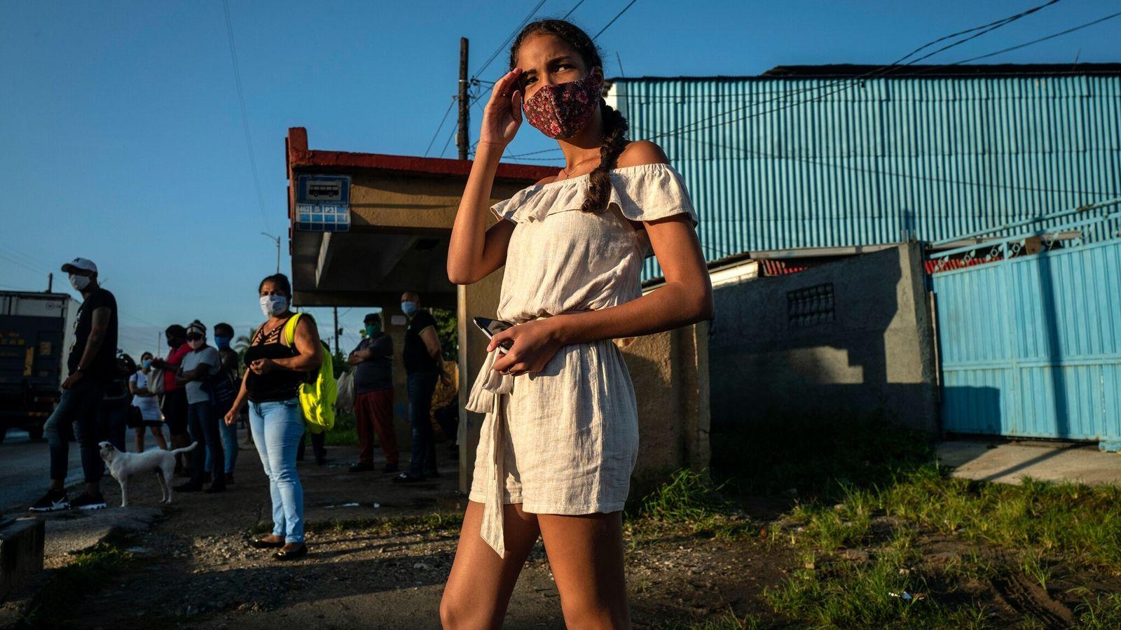 Karla González espera el autobús que la llevará a comprar suministros para sus quince años, la ...