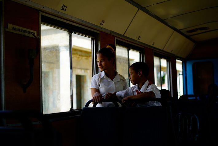 Pequeños estudiantes miran por las ventanas en la estación de tren de San Antonio de los ...
