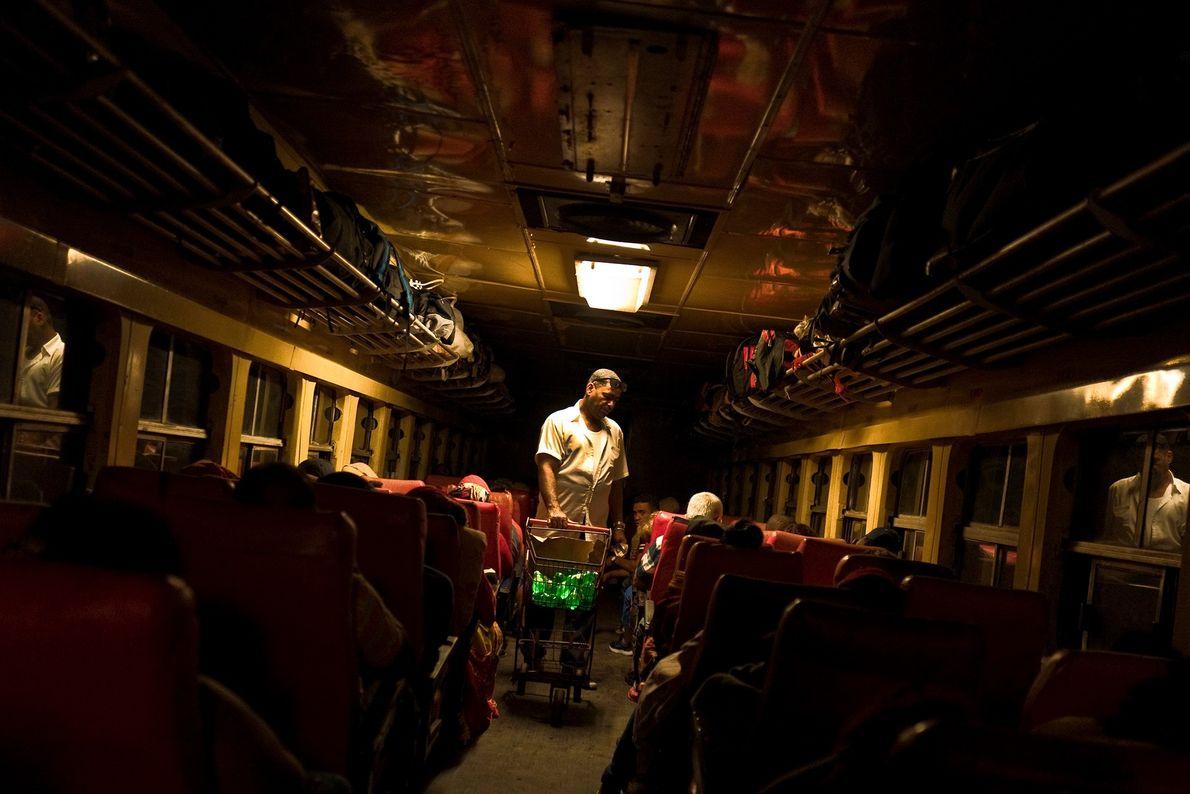 Un hombre vende alimentos a los pasajeros en un viaje nocturno desde La Habana a Santiago ...