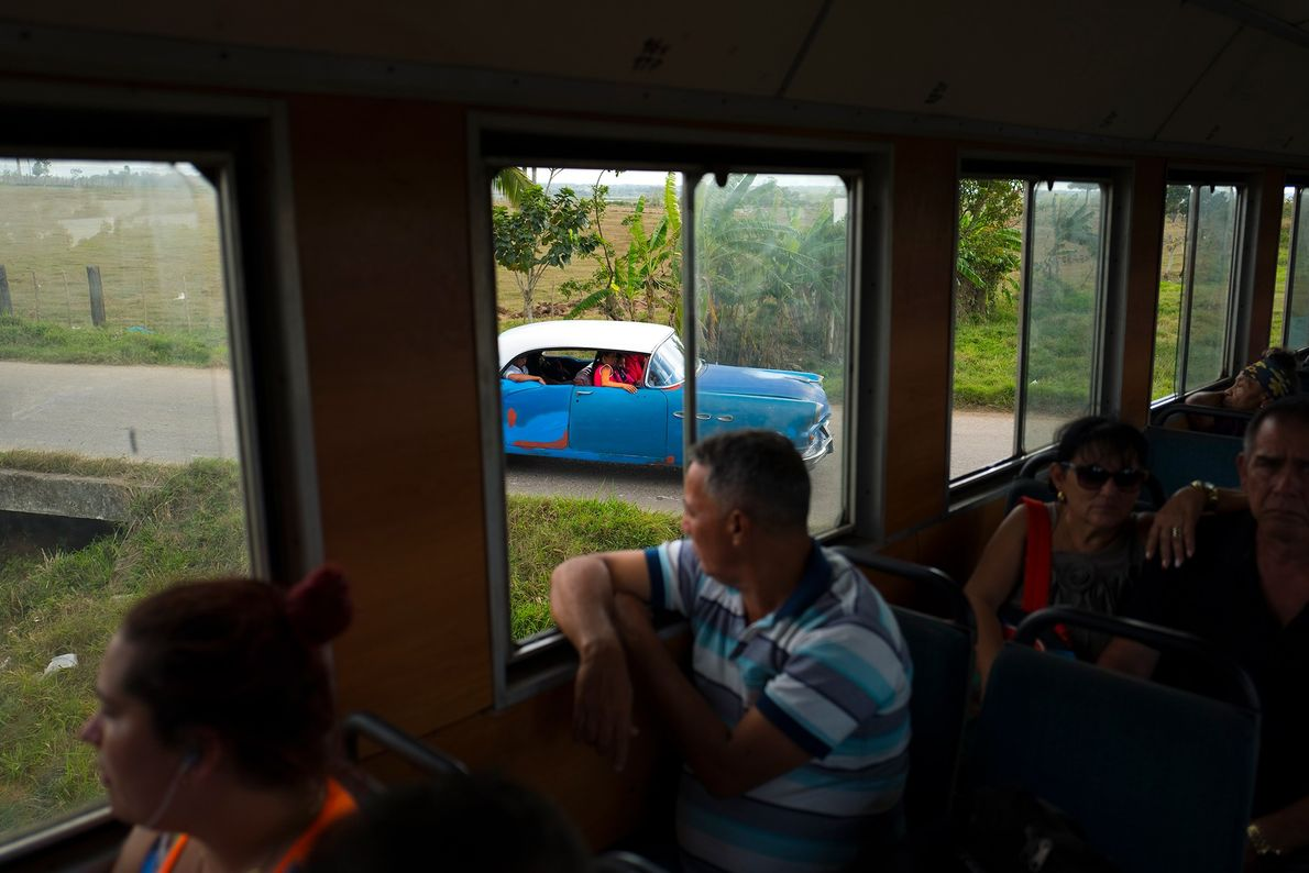 Un coche espera que pase el tren que va a San Antonio de los Baños.