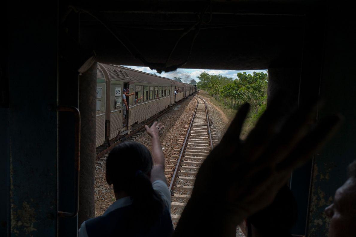 Viajeros se saludan desde las ventanas del tren.