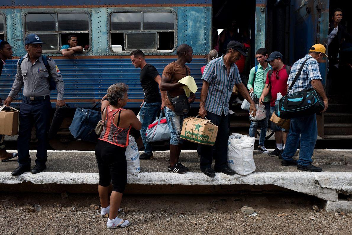 Pasajeros bajan del tren con sus bolsos y paquetes en la estación de Camagüey.