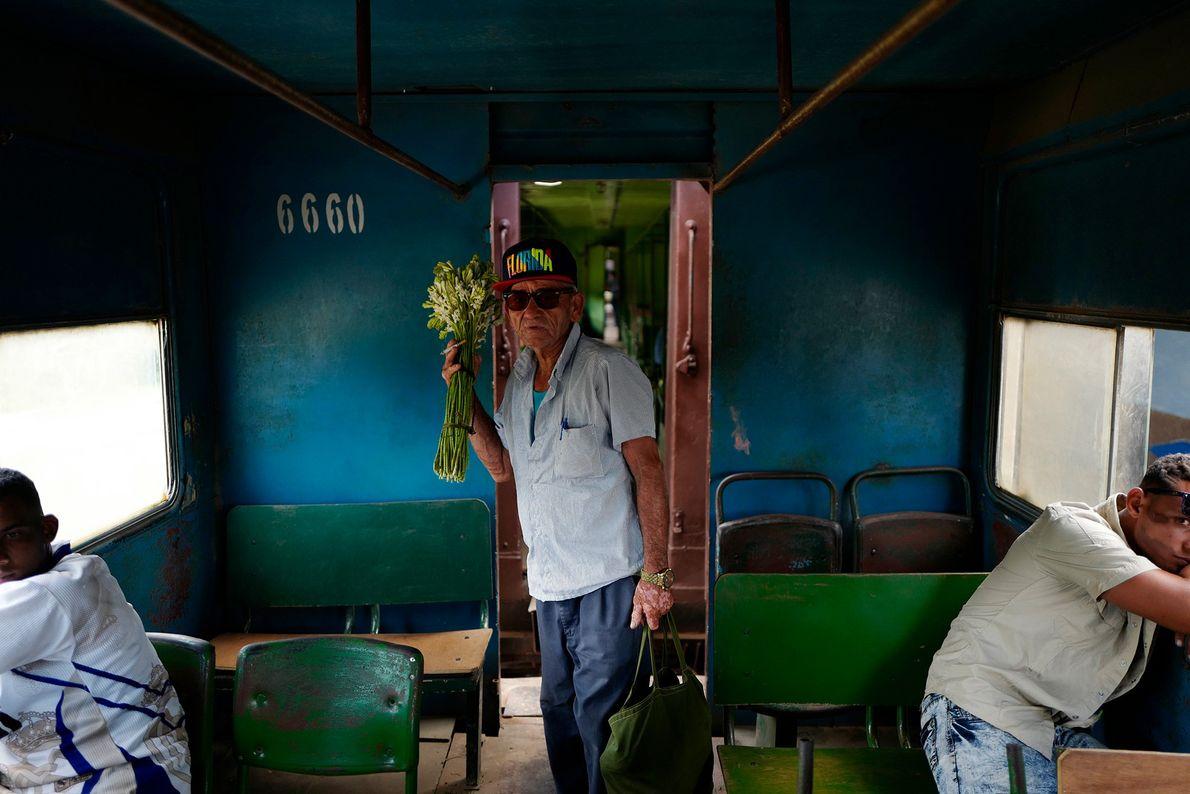 Un hombre con un ramo de flores en el tren que va de Santiago de Cuba ...