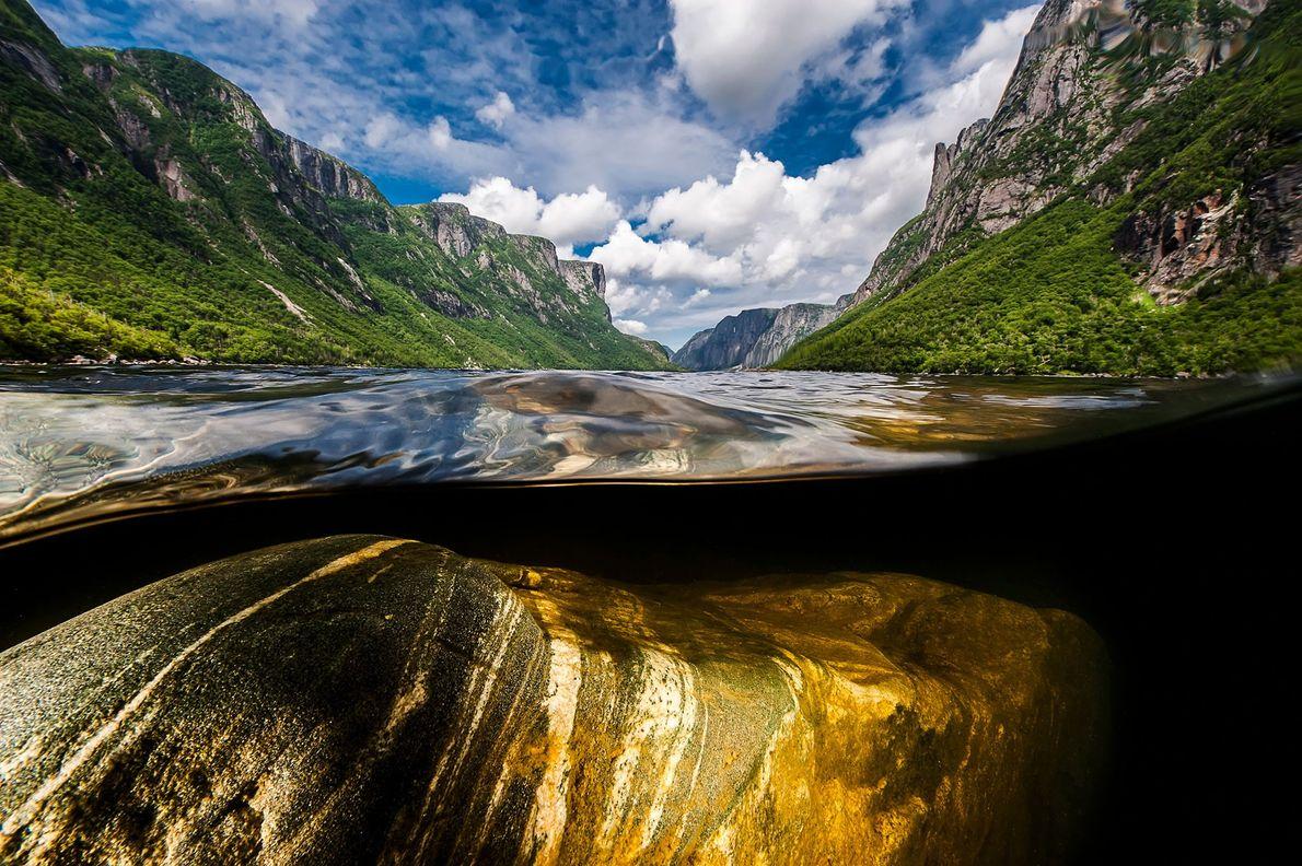 Escarpadas paredes de roca se elevan a 610 metros sobre Western Brook Pond, un fiordo en ...