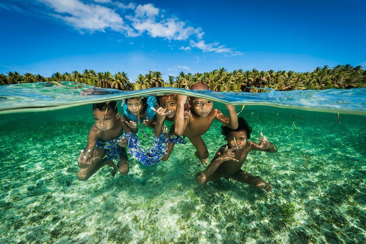 Los descendientes de los legendarios navegantes de la isla Satawal juegan en las aguas cálidas de ...