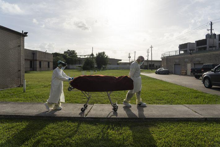 El personal médico que usa EPP completo empuja una camilla con un paciente fallecido a un ...