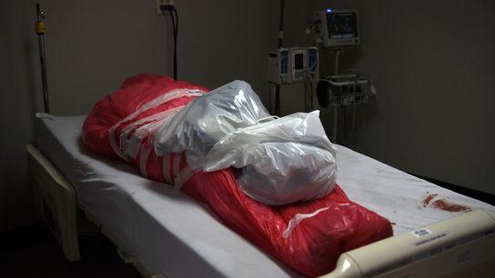 Un hombre que murió a causa del coronavirus se ve envuelto en una bolsa óbito mortuoria ...