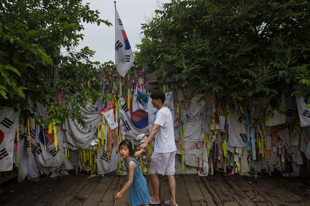 Algunos visitantes cuelgan mensajes y banderas a lo largo de la cerca del Parque de la ...