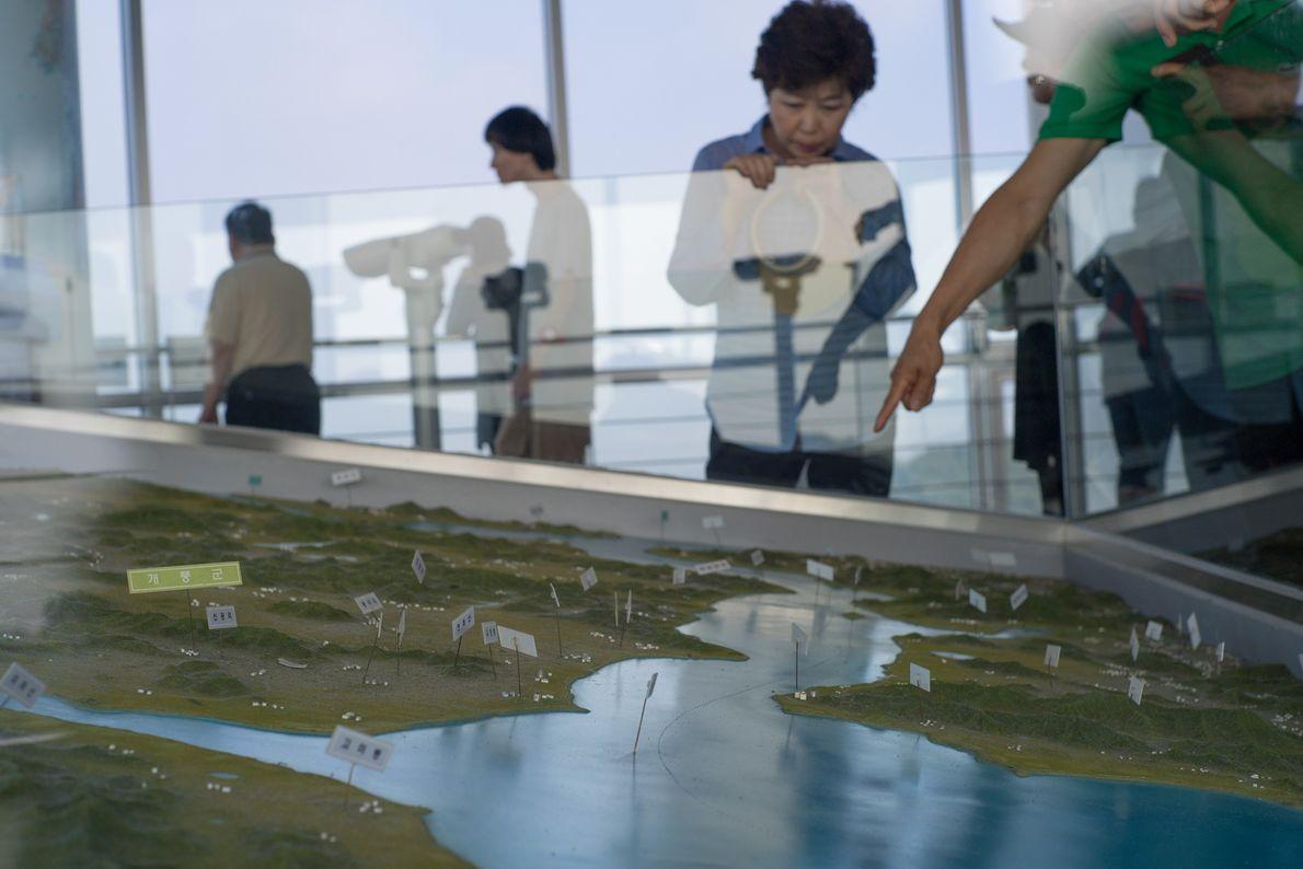 Los visitantes interactúan con exhibiciones en el puesto de observación de Corea del Sur que mira ...