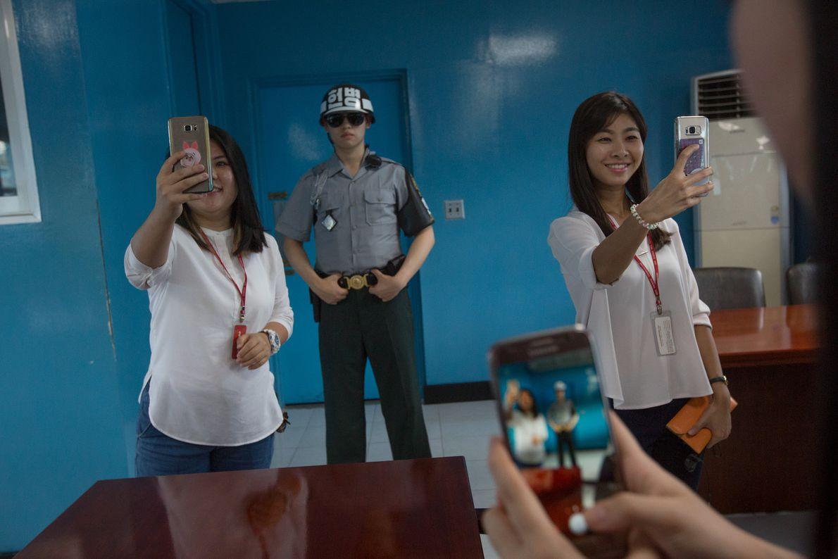 Un soldado permanece inmóvil en el fondo mientras las turistas toman selfies dentro de un edificio ...
