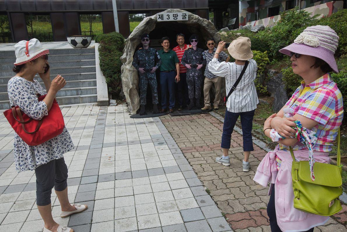 Los visitantes posan con soldados falsos afuera de una réplica de la entrada al Tercer Túnel ...