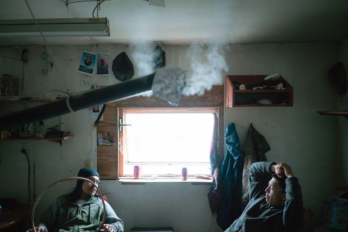 Los primos Justin y Samuel Ahkinga cocen madera al vapor para hacer un tambor tradicional. Doblan ...