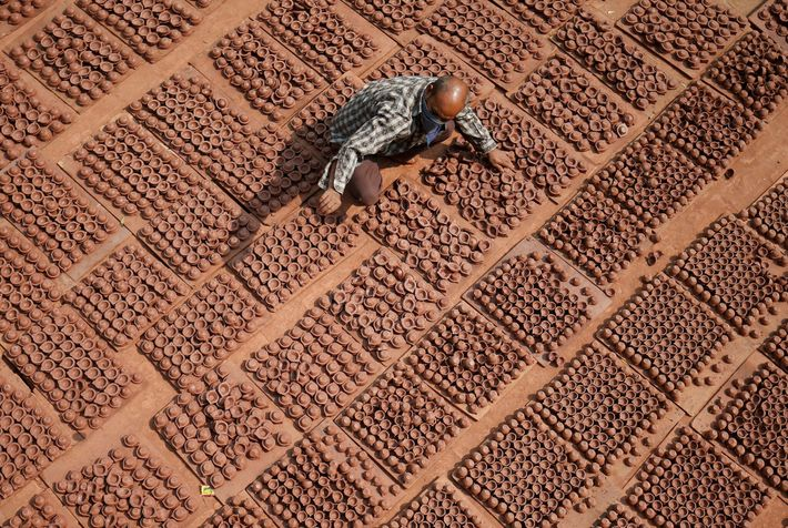 Un alfarero coloca lámparas de barro, con las que se decoran las casas y los templos ...