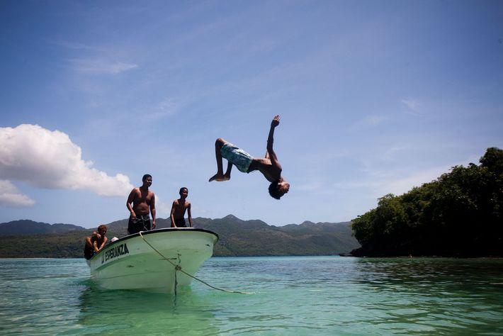 Un joven realiza un backflips desde la proa del bota y se arroja a las aguas ...