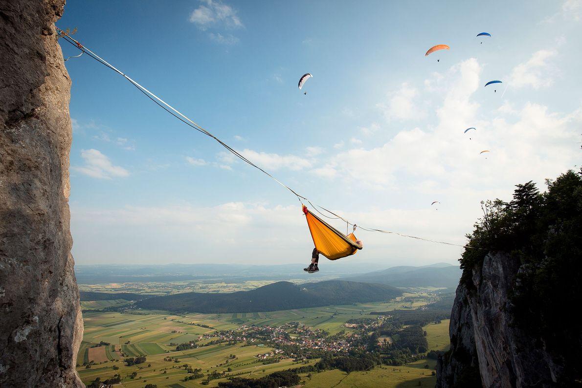 El atleta de highline Thomas Spoettl se toma un descanso en un highline en los Alpes ...