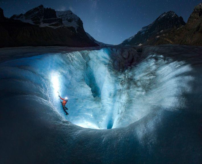 Bajo el cielo nocturno, un escalador de hielo asciende sobre el glaciar Athabasca, que está desapareciendo ...