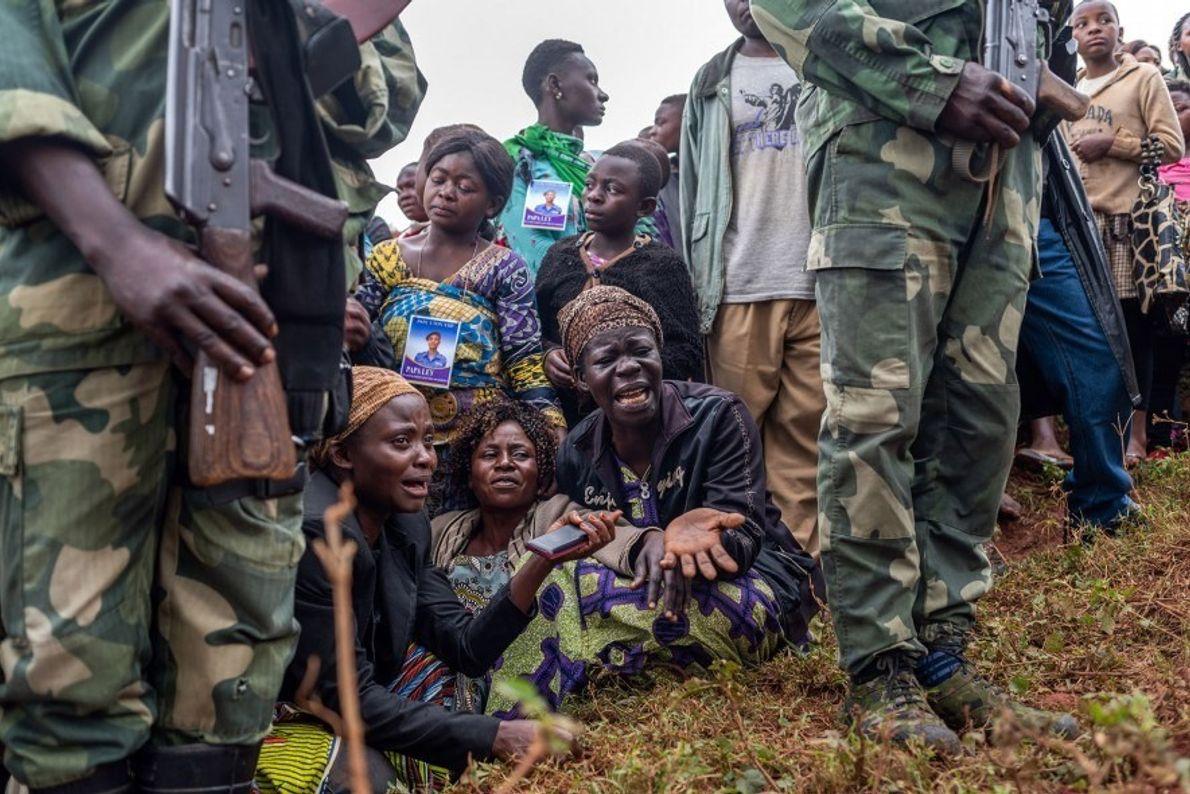 Amigos y familiares del agente de policía Tabu Amuli Emmanuel lloran durante su entierro en el ...