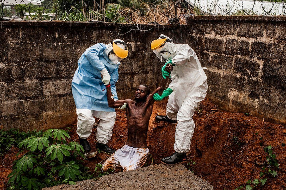 El personal médico del Centro de Tratamiento del Ébola en Hastings, en Sierra Leona, acompaña a ...
