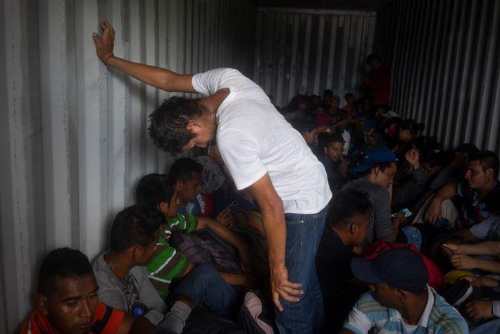 Cientos de migrantes salvadoreños que se unieron a la caravana viajan dentro de un contenedor, mientras ...