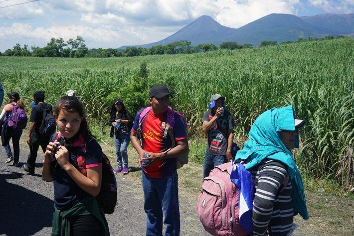 Migrantes salvadoreños estaban alineados al borde de la carretera cerca del volcán Izalco en Sonsonate, El ...