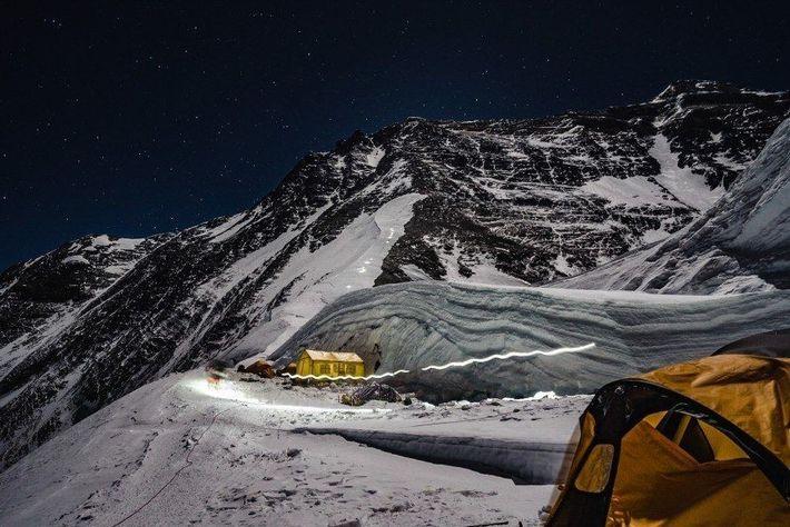 Las linternas frontales de los escaladores iluminan un sendero que asciende por el flanco inferior del ...