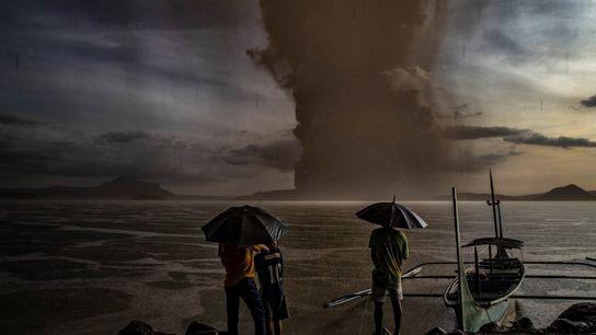 Una nube de ceniza se cierne sobre el lago mientras el volcán Taal entra en erupción ...