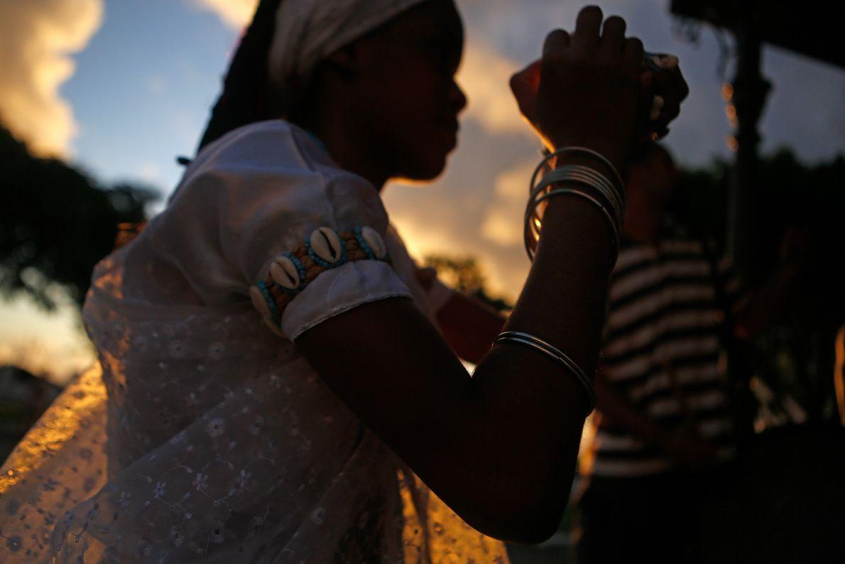 Un miembro femenino de la religión africana-brasilera Candomblé arroja palomitas de maíz a los peatones, un ...