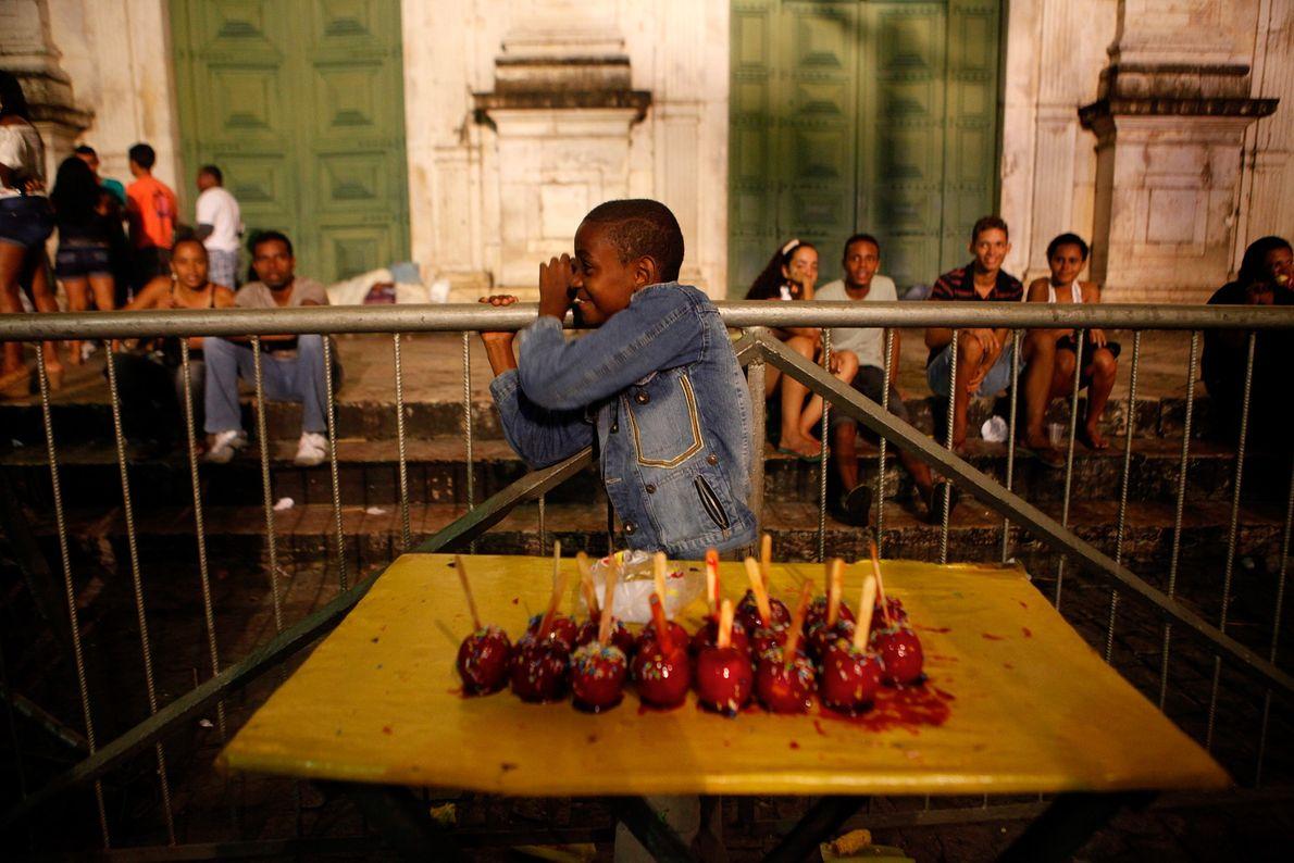 Un niño vende manzanas acarameladas durante los festivales de São João afuera de la catedral de ...