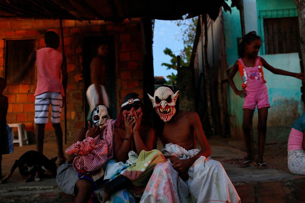 Los niños disfrazados con máscaras y sábanas están sentados en su pórtico de entrada en la ...