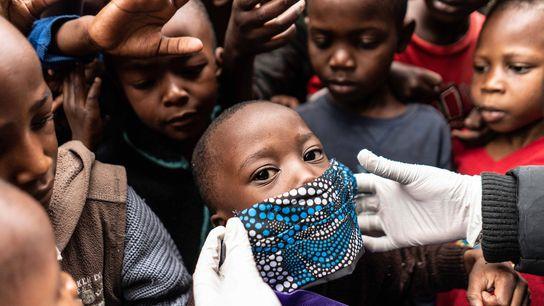 Un trabajador humanitario le coloca una máscara a un niño mientras reparte alimentos a las familias ...