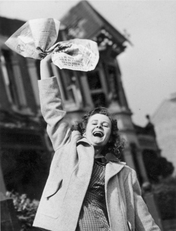 Pat Burgess agita un periódico que proclama la victoria de los aliados con la esperanza de ...