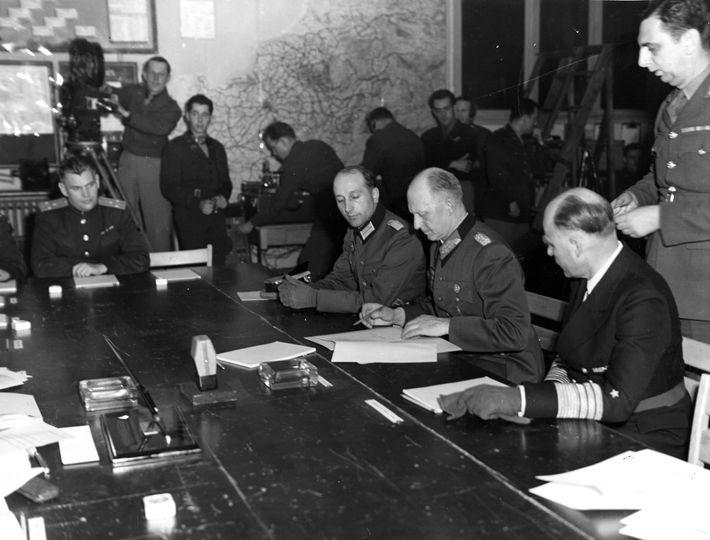 Alfred Jodl, jefe del mando de operaciones de las Wehrmacht, firma un acta de capitulación militar incondicional ...