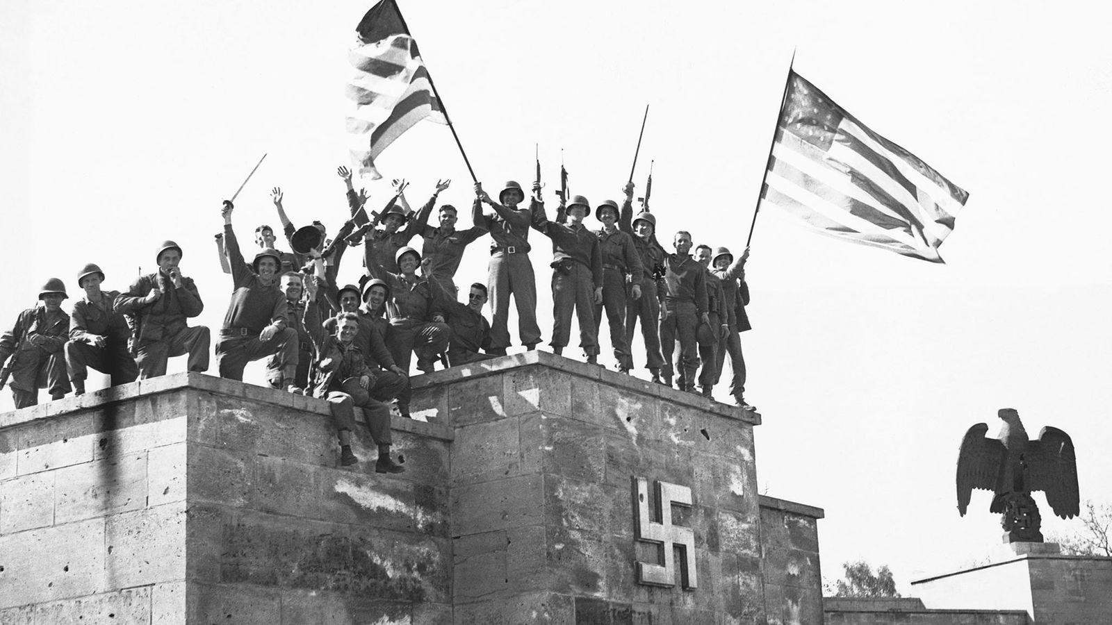 Los soldados estadounidenses celebran la primera rendición incondicional de Alemania, que entró en vigor el 8 ...