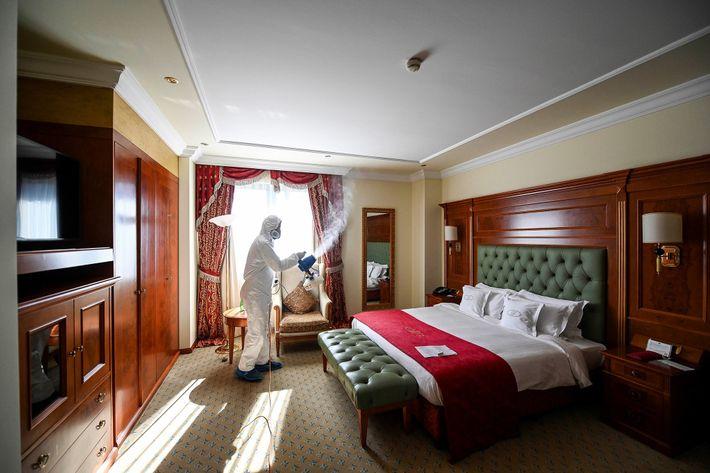 En Pristina, Kosovo, un empleado, vestido con traje protector, desinfecta una habitación de hotel para evitar ...