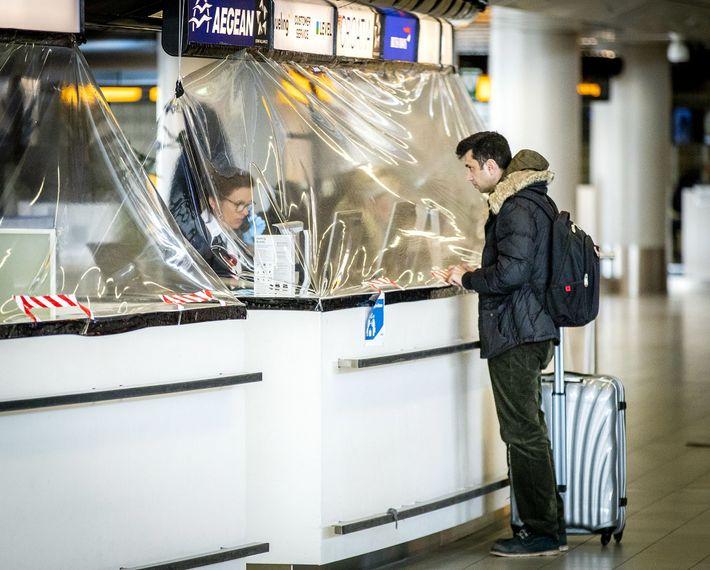 Una cortina de plástico cubre el mostrador de una aerolínea en el aeropuerto Schiphol de Amsterdam ...