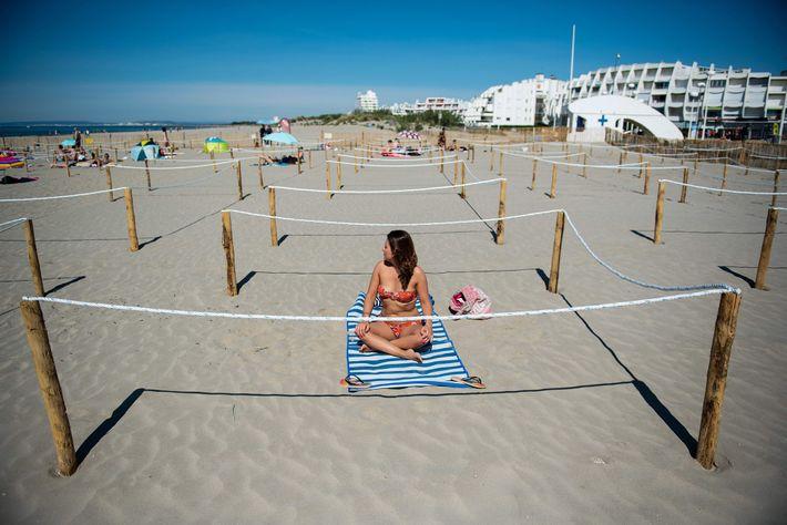 Una mujer toma sol en un área limitada con sogas en la playa de La Grande ...