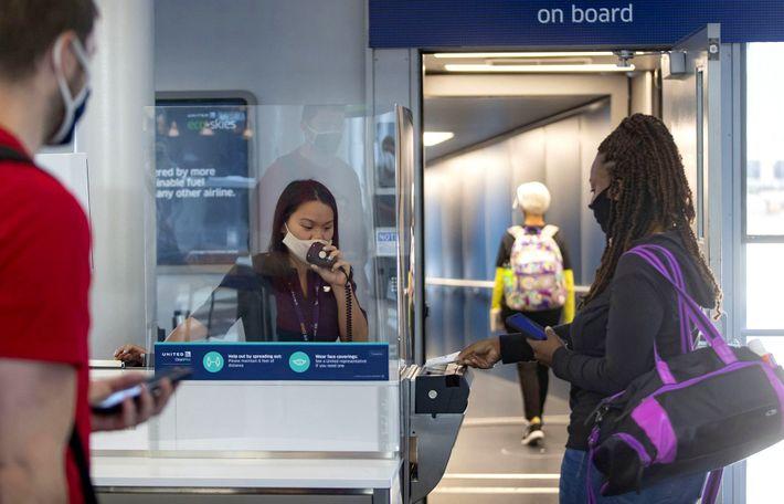 Un agente de puerta de United Airlines ayuda a los pasajeros detrás de un escudo protector ...